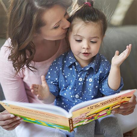 Maman lit un livre personnalisé à sa fille sur les animaux de la ferme